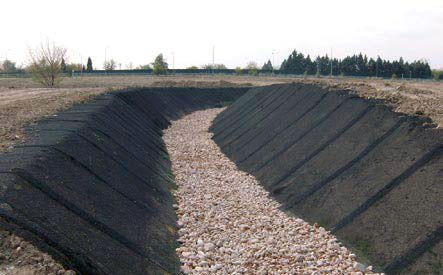 Channelling of the Rejas Stream, with gravel at the channel bottom and slopes upholstered with geogrid hydro-seeded.